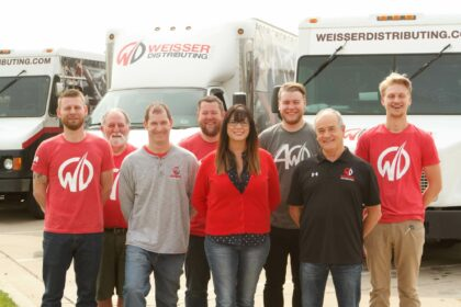 Smiling group of Weisser Distributing employees in Weisser Distributing apparel, standing in front of Weisser trucks.